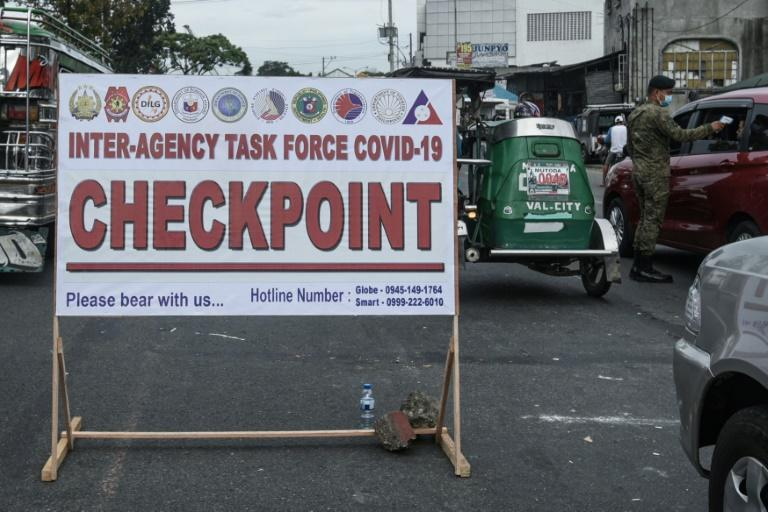 Checkpoint signage is seen in the Philippines as a soldier (R) checks the temperature of a motorist before entering Manila