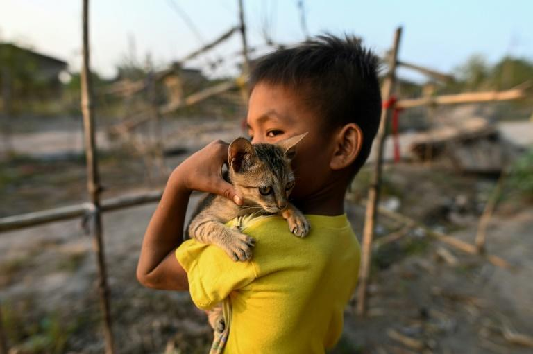 A Chin child plays with his cat in Bethel village
