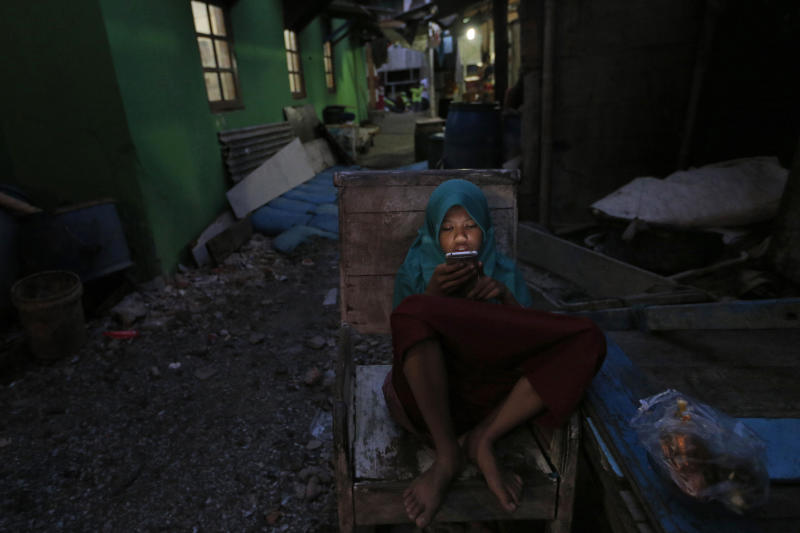 In this Tuesday. Oct. 15, 2019, photo, a girl checks her mobile phone at a slum in Jakarta, Indonesia. Known for his down-to-earth style with a reputation for clean governance, Indonesian President Joko Widodo's signature policy has been improving Indonesia's inadequate infrastructure and reducing poverty, which afflicts close to a tenth of Indonesia's nearly 270 million people. But raising money would be harder at a time of global economic slowdown, major trade conflicts and falling exports. (AP Photo/Tatan Syuflana)