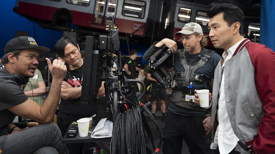 """Director Destin Daniel Cretton, fight instructor Alan Tang, crew camera operator, and Simu Liu on the set of """"Shang-Chi and the Legend of the Ten Rings."""" - Credit: Jasin Boland / Courtesy of Marvel Studios"""