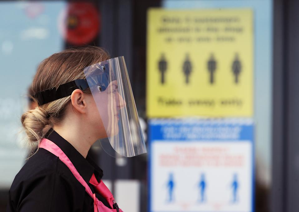 Staff at the Coastline fish and chip shop and ice cream parlour on Blyth beach, Northumberland, wearing personal protective equipment (PPE) as they put out social distancing signs for customers. The restaurant has re-opened for take away orders after the easing of lockdown restrictions during the coronavirus pandemic. (Photo by Owen Humphreys/PA Images via Getty Images)