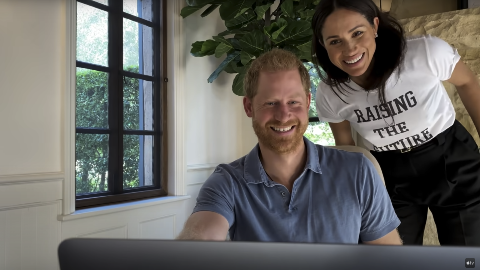 Harry's wife Meghan Markle is seen leaning over Harry while wearing a T-shirt