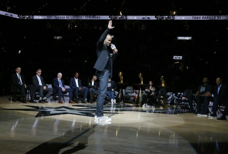 Retired San Antonio Spurs star guard Tony Parker waves to spectators during a ceremony Monday at which the NBA club retired his number nine jersey