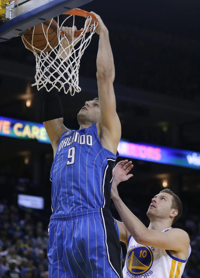 Orlando Magic center Nikola Vucevic (9) scores over Golden State Warriors' David Lee, right, during the first half of an NBA basketball game Tuesday, March 18, 2014, in Oakland, Calif. (AP Photo/Ben Margot)
