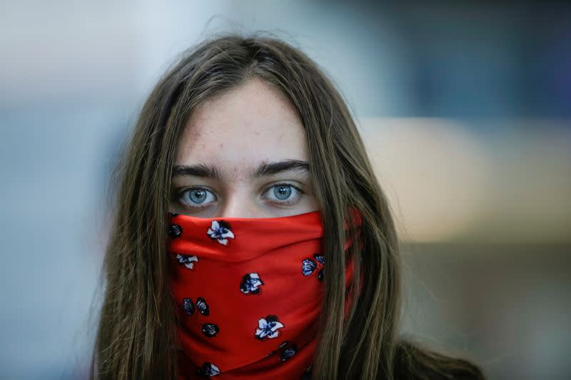 FILE PHOTO: A tourist with covered face waits to check in for her flight at Juan Santamaria International Airport , as Costa Rica tourism industry braces for coronavirus disease (COVID-19) outbreak, in Alajuela