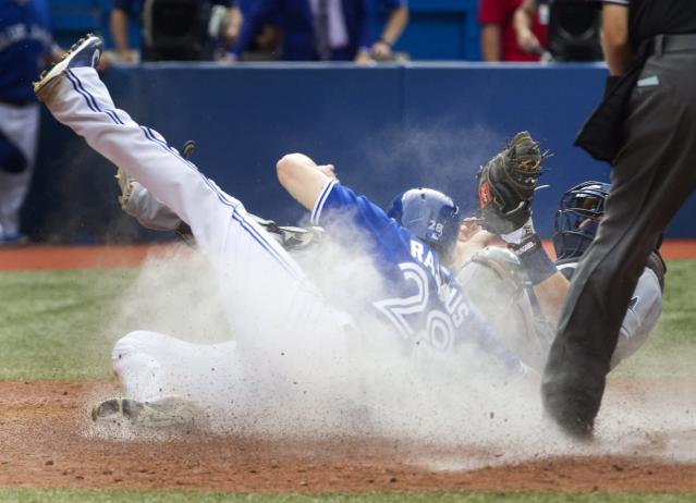 Toronto Blue Jays' Colby Rasmus scores the game-winning run as Tampa Bay Rays catcher Curt Casali is unable to make the play in the 10th inning of a baseball game in Toronto, Saturday, Aug. 23, 2014. The Jays won 5-4 in 10 innings. (AP Photo/The Canadian Press, Fred Thornhill)