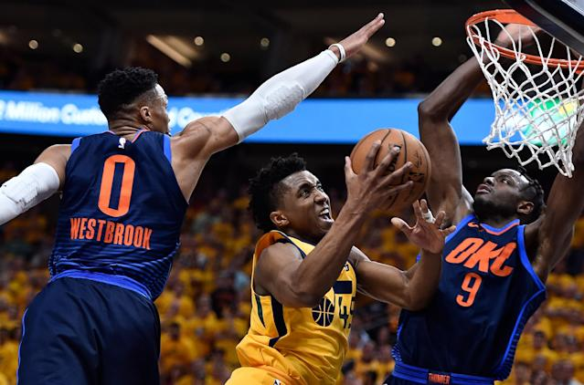 Donovan Mitchell slices between the defense of Russell Westbrook (left) and Jerami Grant as he heads to the basket during the Jazz's Game 6 win over the Thunder. (Getty)