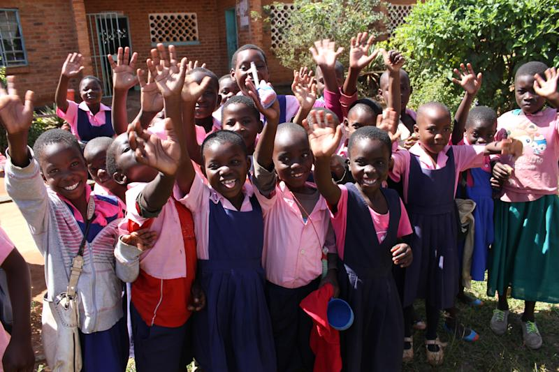 Preeschool students raise their hands for the camera. (Wells for Zoë/Flickr)