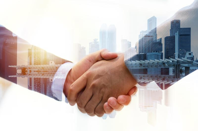 Two people shaking hands with office buildings in the background.