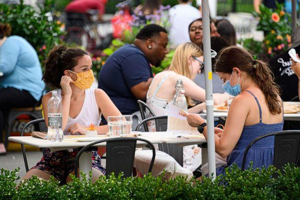 PHOTO: People wear protective face masks at an outdoor restaurant in the Flatiron District as the city continues Phase 4 of re-opening following restrictions imposed to slow the spread of coronavirus on July 26, 2020 in New York City. (Noam Galai/Getty Images)