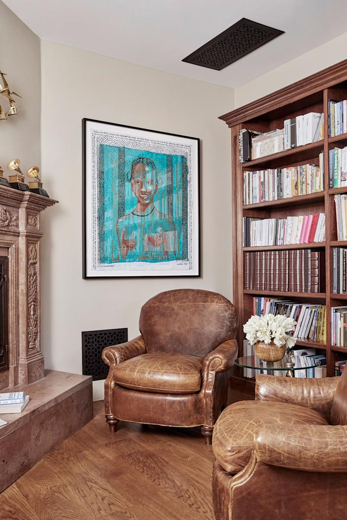 "<div class=""caption""> The library features a cozy nook with leather club chairs from Acquisitions by Henredon, custom-made cherry cabinets, and a hand-carved travertine fireplace. The art is <em>The Sovereign People</em> by Tony Ramos. </div>"