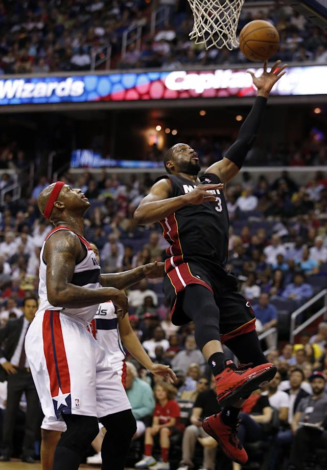 Miami Heat guard Dwyane Wade (3) shoots in front of Washington Wizards forward Al Harrington (7) in the first half of an NBA basketball game, Monday, April 14, 2014, in Washington. (AP Photo/Alex Brandon)