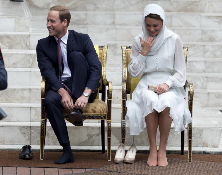 Prince William and his wife Kate, the Duke and Duchess of Cambridge take their shoes off before entering a mosque in Kuala Lumpur, Malaysia, Friday, Sept. 14, 2012. (AP Photo/Mark Baker)