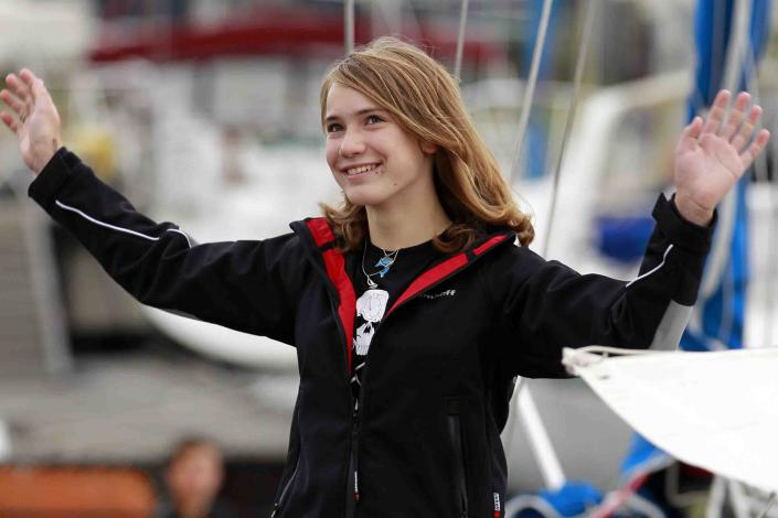 Laura Dekker waves to the media as she stands on her boat in Den Osse, southwest Netherlands, Wednesday, Aug. 4, 2010. Fourteen year-old Laura Dekker, who hopes to become the youngest person to sail around the world by herself, and her father Dick Dekker have departed the harbor of Den Osse in her 38-foot (11.5-meter) yacht Guppy, bound for Portugal where she hopes to begin her solo attempt later this year. (AP Photo/Bas Czerwinski)