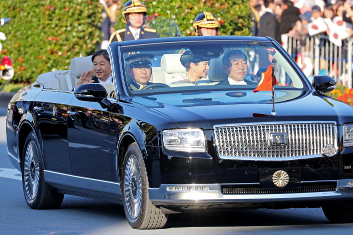 Japanese Emperor Naruhito, left, and Empress Masako, right, wave to spectators during a royal motorcade in Tokyo, Sunday, Nov. 10, 2019. (AP Photo/Koji Sasahara)