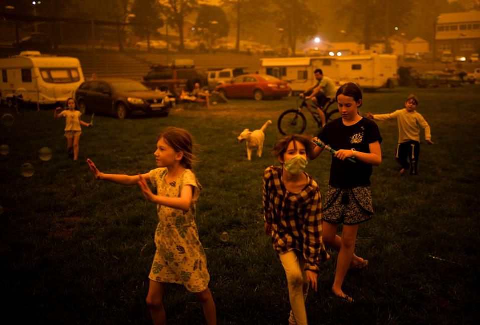 Children play at the showgrounds in the southern New South Wales town of Bega where they are camping after being evacuated from nearby sites affected by bushfires on December 31, 2019. - Thousands of holidaymakers and locals were forced to flee to beaches in fire-ravaged southeast Australia on December 31, as blazes ripped through popular tourist areas leaving no escape by land. (Photo by SEAN DAVEY / AFP) (Photo by SEAN DAVEY/AFP via Getty Images)