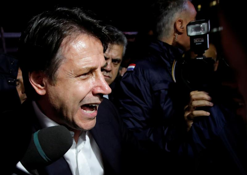 Italian Prime Minister Giuseppe Conte speaks to protesters as he visits the Ilva steel plant, which ArcelorMittal is threatening to abandon over a legal row with the government, in Taranto, Italy, November 8, 2019. REUTERS/Ciro De Luca