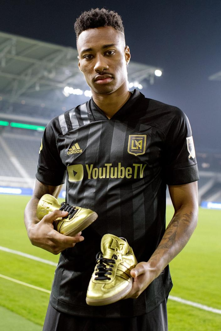 """LAFC midfielder Mark-Anthony Kaye holds a pair of limited-edition Adidas Originals X LAFC sneakers in the Heart of Gold colorway that will be given to community heroes and front-line workers. <span class=""""copyright"""">(Adidas Creators Network)</span>"""
