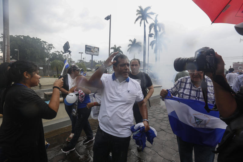 "People turn away as police launch tear gas to disperse demonstrators at an anti-government march dubbed, ""Nothing is Normal"" in honor of slain student Matt Romero, in Managua, Nicaragua, Saturday, Sept. 21, 2019. 16-year-old Matt Romero was killed during ""crossfire"" last September when armed men wearing hoods clashed with anti-government protesters. (AP Photo/Alfredo Zuniga)"