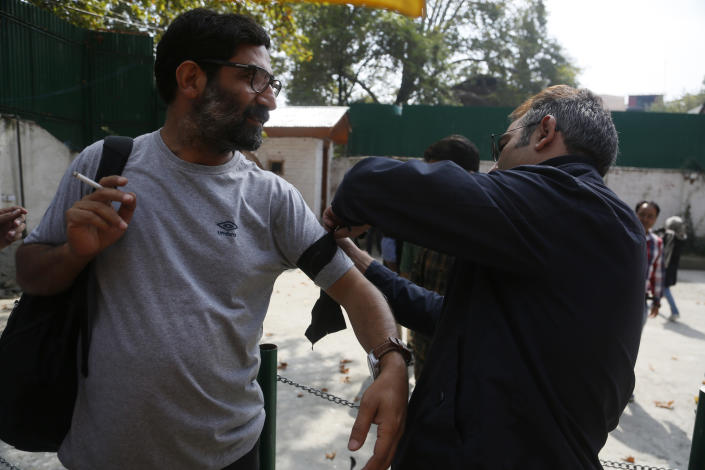 A Kashmiri journalist ties a black band on a colleague before a protest against the communication blackout in Srinagar, Indian controlled Kashmir, Thursday, Oct. 3, 2019. For the last two months, mobile phones and internet services have been shut down in the valley after New Delhi stripped Indian-controlled Kashmir of its semi-autonomous powers and implemented a strict clampdown, snapping communications networks, landlines and mobile Internet. (AP Photo/Mukhtar Khan)