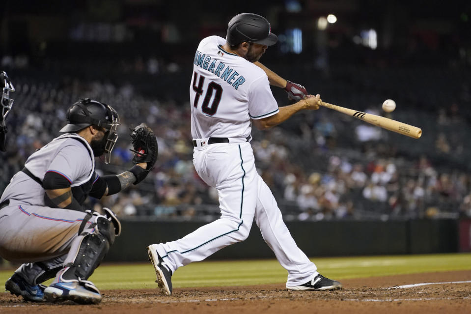 Arizona Diamondbacks' Madison Bumgarner (40) connects for a sacrifice fly during the fifth inning of a baseball game against the Miami Marlins, Tuesday, May 11, 2021, in Phoenix. (AP Photo/Matt York)