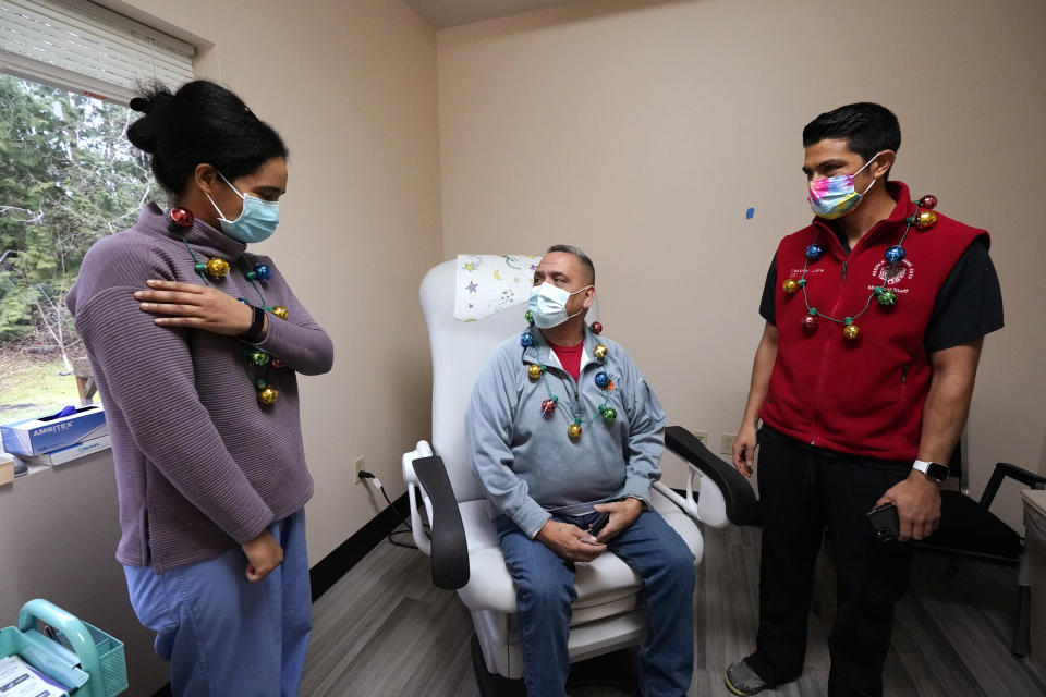 Dr. Dakotah Lane, right, looks on as Dr. Cristina Toledo-Cornell explains possible arm soreness to James Scott after Scott received the first COVID-19 vaccination given to a Lummi Nation tribal member Thursday, Dec. 17, 2020, on the Lummi Reservation, near Bellingham, Wash. The Native American tribe began rationing its first 300 doses of vaccine as it fights surging cases with a shelter-in-place order. (AP Photo/Elaine Thompson)