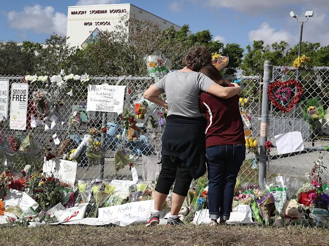 <p>Margarita Lasalle (R), the budget keeper, and Joellen Berman, Guidance Data Specialist, look on at the memorial in front of Marjory Stoneman Douglas High School as teachers and staff are allowed to return to the school for the first time since the mass shooting on campus on February 23, 2018 in Parkland, Fla. (Photo: Joe Raedle/Getty Images) </p>