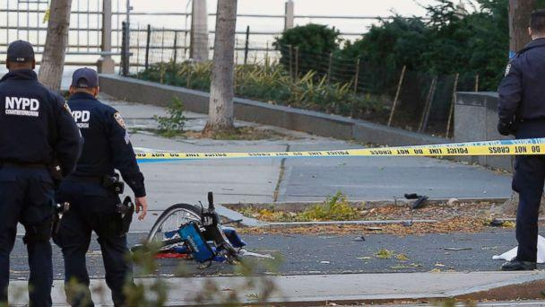 PHOTO: A New York Police Department officer stands next to a body covered under a white sheet near a mangled bike along a bike path, Oct. 31, 2017, in New York. (Bebeto Matthews/AP)