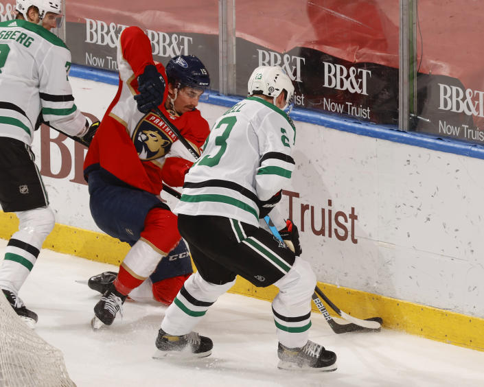 Florida Panthers left wing Mason Marchment (19) and Dallas Stars defenseman Esa Lindell (23) battle for control of the puck during the second period of an NHL hockey game, Monday, May 3, 2021, in Sunrise, Fla. (AP Photo/Joel Auerbach)