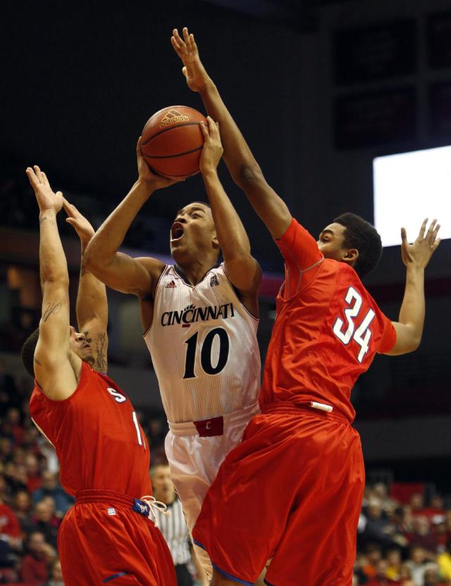 Cincinnati guard Troy Caupain (10) looks to shoot under pressure from SMU guard Nic Moore (11) and forward Ben Moore (34) during the first half of an NCAA college basketball game, Wednesday, Jan. 1, 2014, in Cincinnati. (AP Photo/David Kohl)