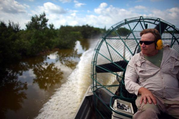 Joe Wasilewski drives an airboat as he checks on crocodile nests near the Florida Power & Light's Turkey Point Nuclear Power Plant where they protect the crocodile and conduct research by counting their nests annually to record population changes June 28, 2012 near Florida City, Florida. Wasilewski, a biologist, studies the reptile and helps in developing and constructing the American crocodile nesting habitat near the power plant. The American crocodile had been on the endangered species list but has been taken off that list and put on the threatened list. With the success of the program to help save the crocodile their populations around developed areas will continue to grow which means that there may be more encounters between humans and the reptile. (Photo by Joe Raedle/Getty Images)