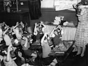 <p>During World War II an elementary school teacher shows her students how to use a gas mask in case of an attack.</p>