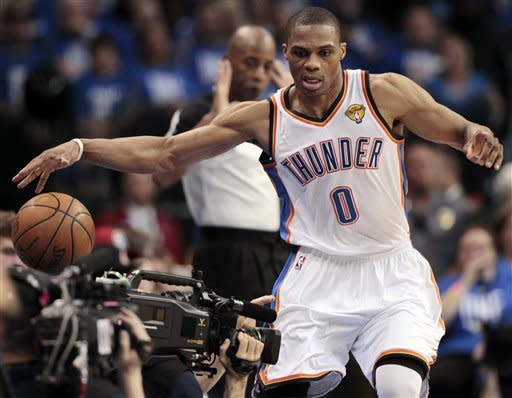 Oklahoma City Thunder point guard Russell Westbrook (0) tries to keep the ball from going out against the Miami Heat during the first half at Game 1 of the NBA finals basketball series, Tuesday, June 12, 2012, in Oklahoma City. (AP Photo/Jeff Roberson)