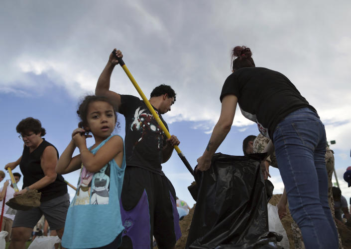 <p>Aria Gonzalez, 3, waits patiently as her parents Jamina, right, and Edwin, center, fill trash bags with sand provided by the city on Sept 11, 2018, in Virginia Beach, Va. The city dumped mounds of free sand in one of the parking lots at the Virginia Beach Sportsplex for residents to use ahead of Hurricane Florence. (Photo: Vicki Cronis-Nohe/The Virginian-Pilot via AP) </p>