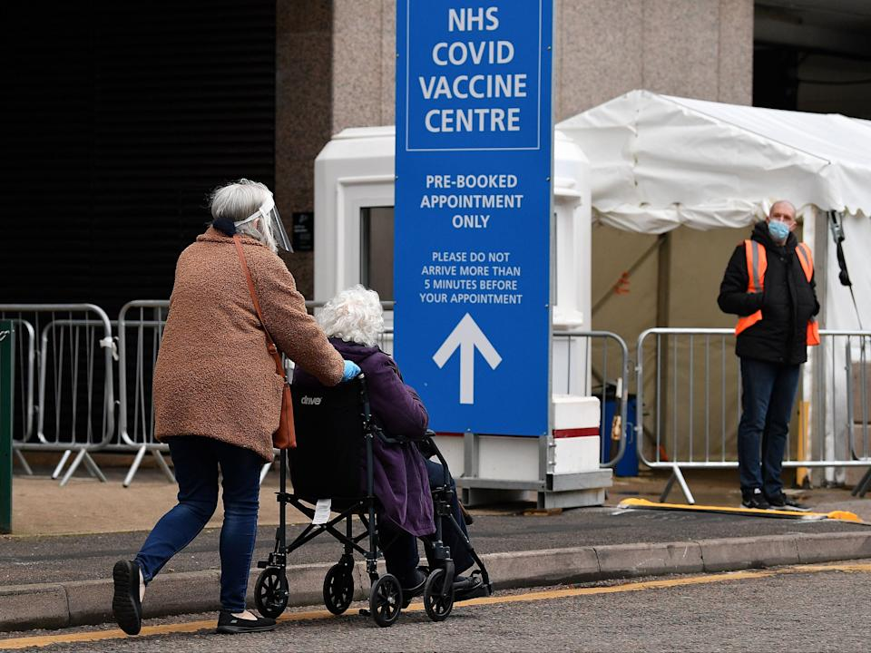 An elderly person in a wheelchair attends a Covid-19 vaccination centre in Wembley, northwest London, on Tuesday (AFP via Getty Images)