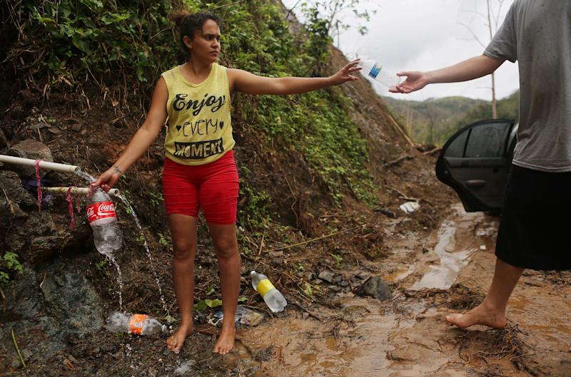 Yanira Rios collects spring water nearly three weeks after Hurricane Maria destroyed her town of Utuado. It's not clear if the water she's collecting is safe to drink.