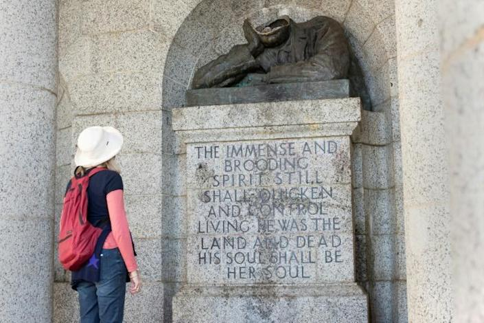 A visitor looks at the decapitated bust of Cecil John Rhodes, a 19th century British colonialist, at the Rhodes Memorial in Cape Town on July 15, 2020. (AFP Photo/RODGER BOSCH)