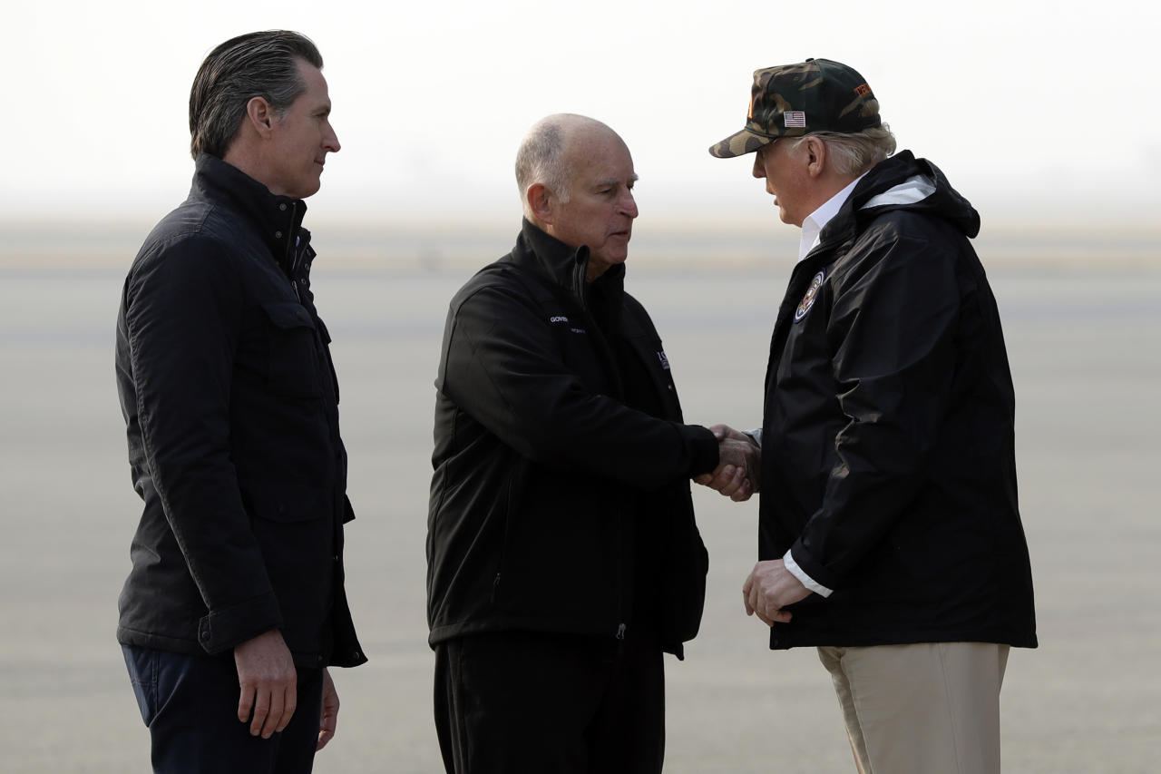 <p>President Donald Trump greets California Gov. Jerry Brown as Gov.-elect Gavin Newsom, left, watches as he arrives on Air Force One at Beale Air Force Base for a visit to areas impacted by the wildfires, Nov. 17, 2018, at Beale Air Force Base, Calif. (Photo: Evan Vucci/AP) </p>