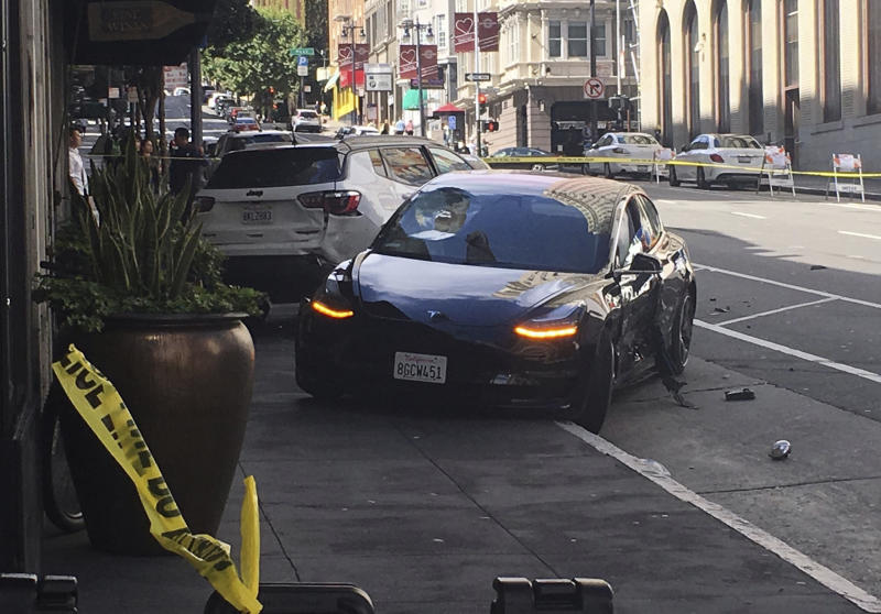 FILE - In this Sunday, July 21, 2019 file photo shows the scene after a woman was arrested after running a red light in a rented Tesla in San Francisco and causing a crash that killed a tourist and left his wife critically injured. San Francisco police said Wednesday, July 24, 2019, preliminary information shows a rented Tesla that was speeding when it ran a red light and struck a couple was not on semi-autonomous Autopilot mode. (Kate Larsen/KGO-TV via AP,File)