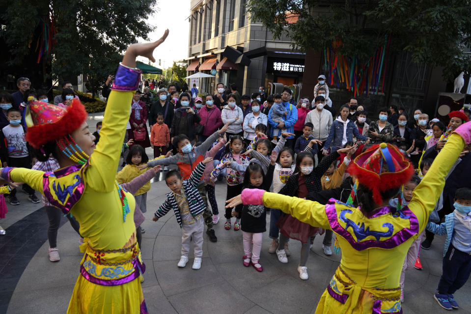 Dancers teach children to dance at a popular shopping town on the outskirts of Beijing on Monday, Oct. 5, 2020. Chinese tourists took 425 million domestic trips in the first half of the eight-day National Day holiday, generating $45.9 billion in tourism revenue, according to China's ministry of culture and tourism. The holiday this year, which coincides with the Mid-Autumn Festival, will be a litmus test of whether China's tourism industry can bounce back after being battered by COVID-19. (AP Photo/Ng Han Guan)
