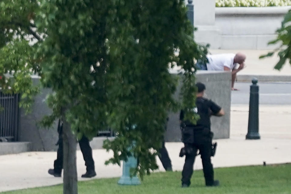 A person is apprehended after being in a pickup truck parked on the sidewalk in front of the Library of Congress' Thomas Jefferson Building, as seen from a window of the U.S. Capitol, Thursday, Aug. 19, 2021, in Washington. Officials evacuated a number of buildings around the Capitol and sent snipers to the area after officers saw a man holding what looked like a detonator inside the pickup, which had no license plates. The man was identified as Floyd Ray Roseberry, 49, of Grover, North Carolina, according to two people briefed on the matter. (AP Photo/Alex Brandon)
