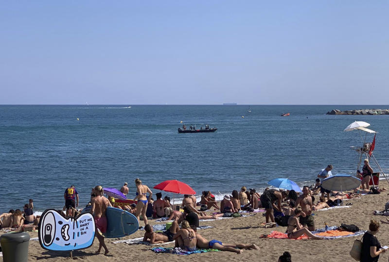 A police boat works after locating possible explosive device in the sea while people sunbathe on an open part of a beach in Barcelona, Spain, Sunday Aug. 25, 2019. Authorities in Barcelona have evacuated one of the Spanish city's popular beaches after reports of a possible explosive device there, though reports indicated it was an old, possibly wartime device and was underwater off the coast. (AP Photo/Ignacio Murillo)