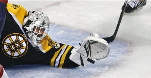 Boston Bruins goalie Tim Thomas (30) reaches out to make a save against the Washington Capitals during the third period of Game 1 of an NHL hockey Stanley Cup first-round playoff series in Boston, Thursday, April 12, 2012. (AP Photo/Charles Krupa)
