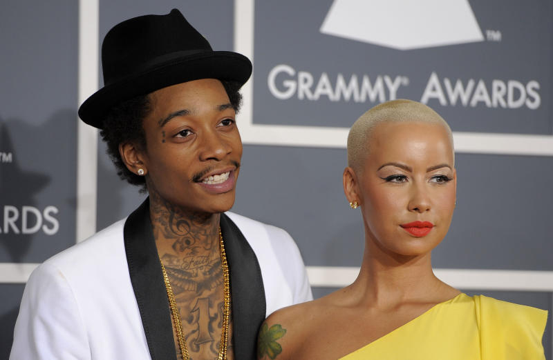 """FILE - This Feb. 12, 2012 file photo shows Wiz Khalifa, left, and Amber Rose at the 54th annual Grammy Awards in Los Angeles. Khalifa says the preparation of becoming a first-time father and husband has helped put him in a more mature musical state of mind. """"I'm at a different point of my life,"""" said Khalifa, whose sophomore album, """"O.N.I.F.C.,"""" debuted at No. 2 on Billboard's 200 albums chart Wednesday with more than 141,000 copies sold, according to Nielsen Scan. (AP Photo/Chris Pizzello, file)"""