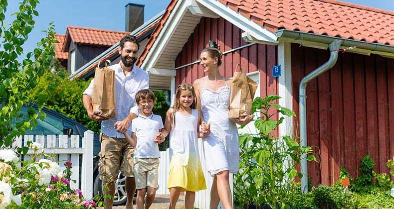 Young familiy holding bag of groceries outside home copyright Kzenon/Shutterstock.com