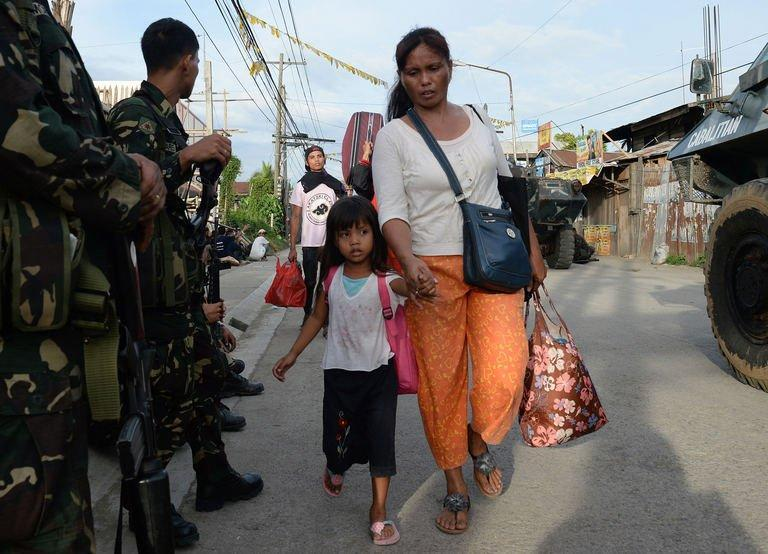 Residents affected by the standoff between Muslim gunmen and army troops walk past soldiers as they evacuate to a safer area in Zamboanga City, on the southern island of Mindanao on September 10, 2013
