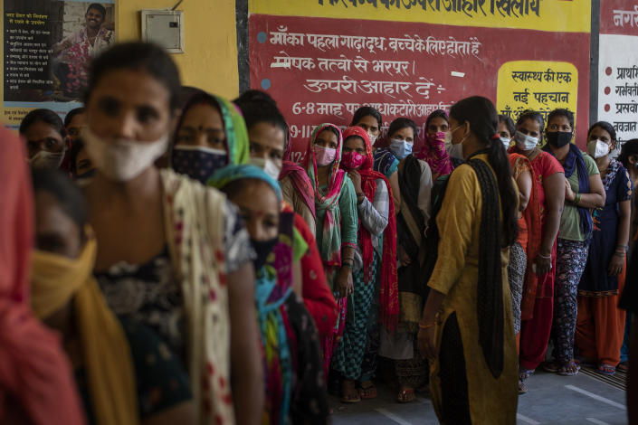 People wait in line for the arrival of vaccines during a vaccination drive against the coronavirus at a government health centre in Noida, a suburb of New Delhi, India, Tuesday, Aug. 3, 2021. (AP Photo/Altaf Qadri)