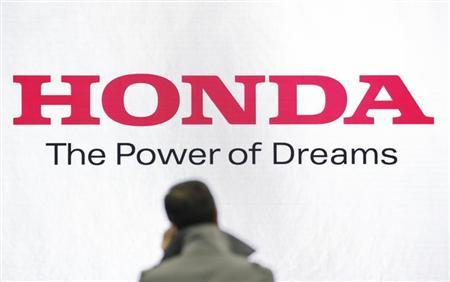 A man stands in front of a logo of Honda Motor at the company showroom in Tokyo