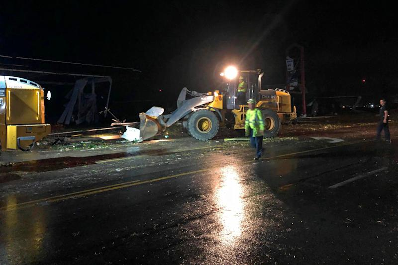 Crews use heavy equipment to push and lift downed power lines, twisted metal and other debris from Ellis Boulevard in Jefferson City, Mo., May 23, 2019. (Photo: AP Photo/David Lieb)