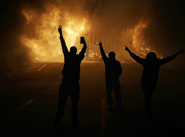 <p>People watch as stores burn in Ferguson, Mo., after a grand jury decided not to indict Ferguson police Officer Darren Wilson in the death of Michael Brown, the unarmed, black 18-year-old whose fatal shooting sparked sometimes violent protests on Nov. 25, 2014. (AP Photo/David Goldman, File) </p>